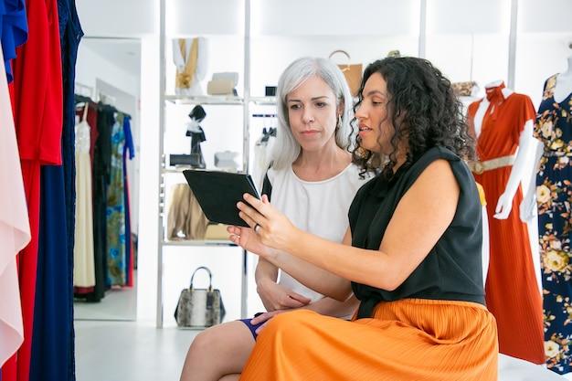 Ernstige klant en winkelbediende ontmoeten elkaar in de modewinkel, zitten samen en gebruiken tablet, bespreken kleding en aankopen. consumentisme of winkelconcept