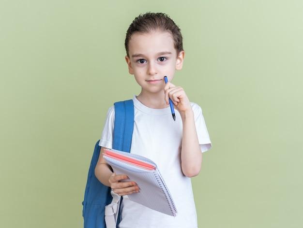 Ernstige kleine jongen die een rugzak draagt met een notitieblok dat zijn gezicht aanraakt met een pen