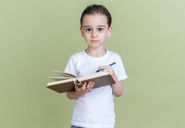 Ernstige kleine jongen kijkt naar camera met boek en pen geïsoleerd op olijfgroene muur met kopieerruimte