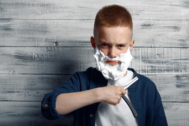 Ernstige kleine jongen met scheerschuim op zijn gezicht houdt een scheermesje in de studio.