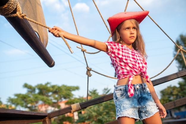 Ernstige kleine meisjespiraat in een geruit overhemd en een spijkerbroek houdt zich vast aan de koorden van het schip