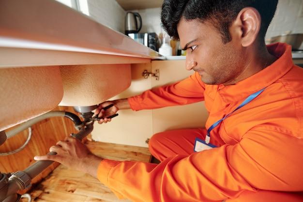 Ernstige klusjesman die een tang gebruikt bij het repareren van een lekkende pijp onder de gootsteen in de keuken van de klant