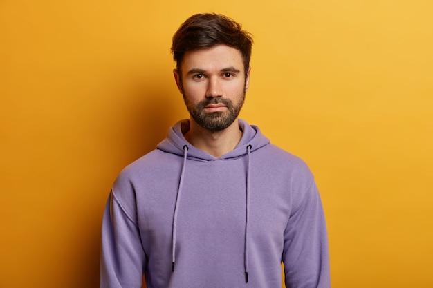 Ernstige knappe bebaarde europese man kijkt recht, heeft dikke haren, draagt paarse hoodie, gekleed in casual hoodie, poseert over gele muur, luistert aandachtig naar informatie.