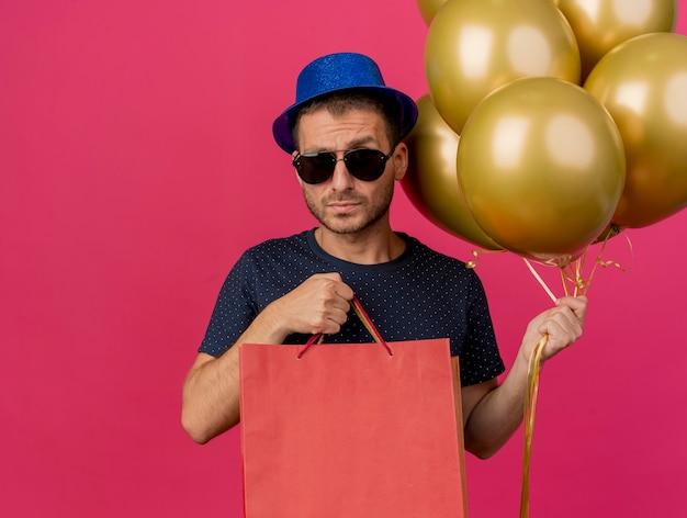 Ernstige knappe blanke man in zonnebril met blauwe feestmuts houdt helium ballonnen en papieren boodschappentassen geïsoleerd op roze achtergrond met kopie ruimte