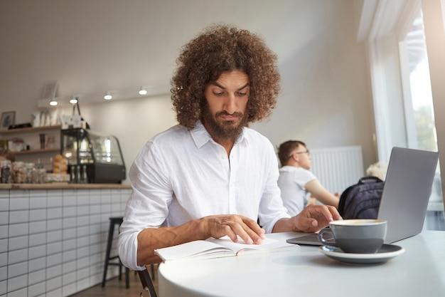 Ernstige knappe gekrulde man met baard op afstand werken met zijn laptop in coffeeshop, aandachtig in zijn aantekeningen kijken en voorhoofd rimpelen