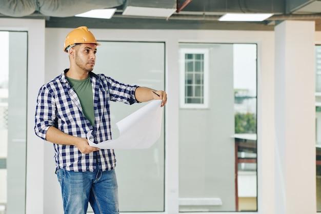 Ernstige knappe jonge bouwingenieur met blauwdruk die servicelijnen in de bouw controleert