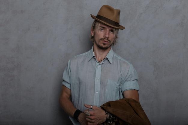 Ernstige knappe jonge hipster man met lederen armbanden met een jas in een bruine hoed in een elegant shirt in spijkerbroek staat in de kamer bij de muur.