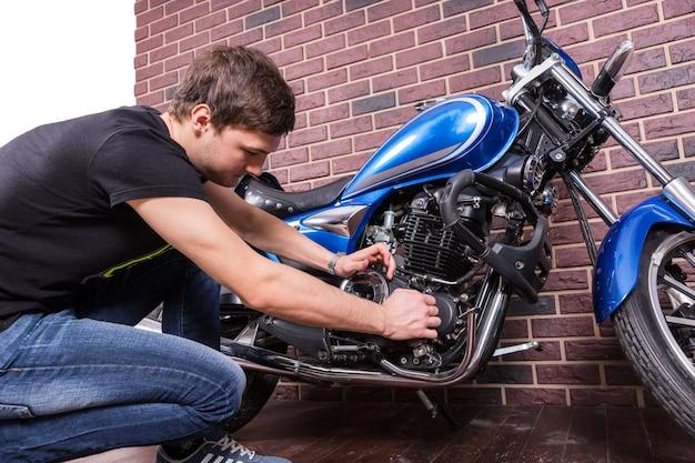 Ernstige knappe jongeman die sommige delen van zijn blauwe motor repareert met zijn blote handen.
