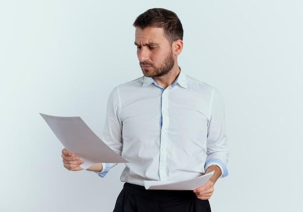 Ernstige knappe man houdt en kijkt naar vellen papier geïsoleerd op een witte muur