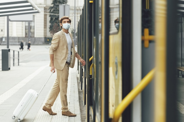 Ernstige knappe man met trendy beige pak en medisch masker staande in de buurt van gele tram met bagage