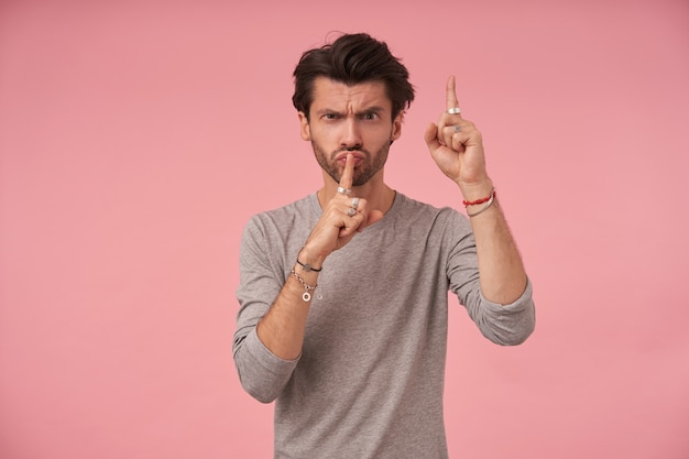 Ernstige knappe man met trendy kapsel, gekleed in grijze trui, poseren met opgeheven wijsvingers in stil gebaar, roepend om te zwijgen, fronsend en tuitende lippen