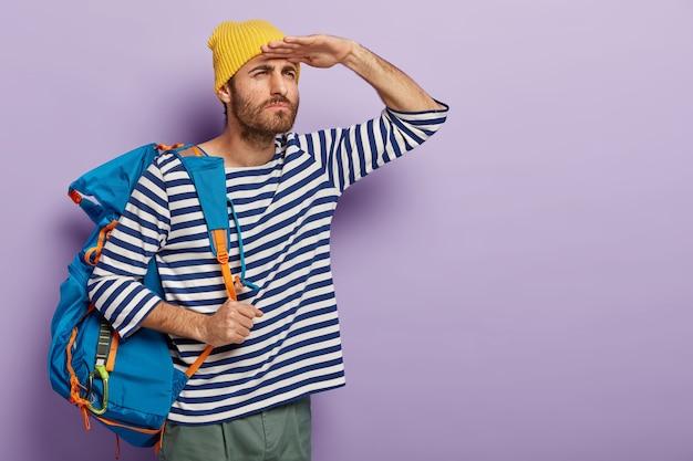 Ernstige knappe man probeert iets in de verte te zien, houdt de handpalmen bij het voorhoofd, draagt een grote toeristenrugzak met persoonlijke spullen