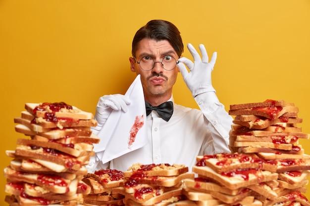 Ernstige knappe ober kijkt nauwgezet door een bril, houdt een vies servet vast, bezig met serveren, omringd door veel smakelijke toast