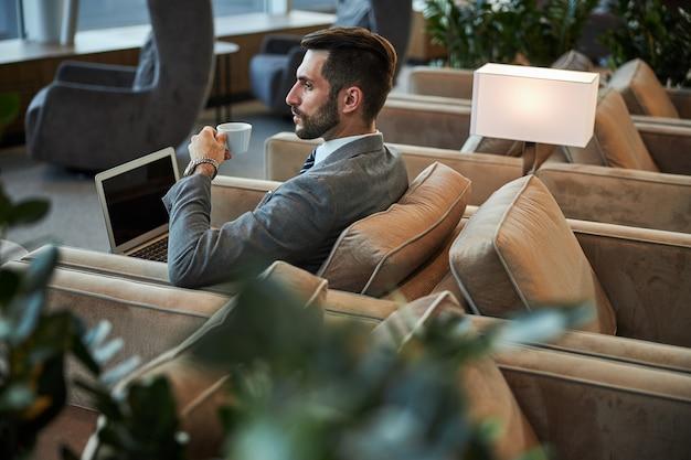 Ernstige knappe persoon die koffie drinkt in de business lounge