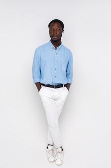 Ernstige knappe stijlvolle man in vrijetijdskleding op geïsoleerde witte muur