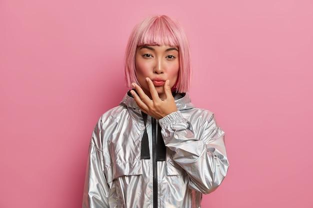 Ernstige knappe vrouw heeft oosterse uitstraling, drukt lippen met de hand, ziet er direct uit, gekleed in een stijlvol zilveren jasje, heeft trendy roze haarstijl, poseert binnen. gezichtsuitdrukkingen