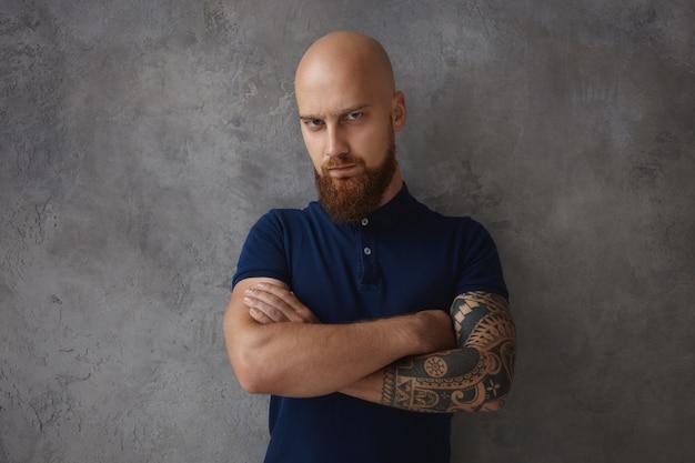 Ernstige krachtige europese man met tatoeage, kaal hoofd en dikke baard fronsend ontevreden ontevreden blik, uiting geven aan zijn negatieve houding, armen gevouwen op de borst