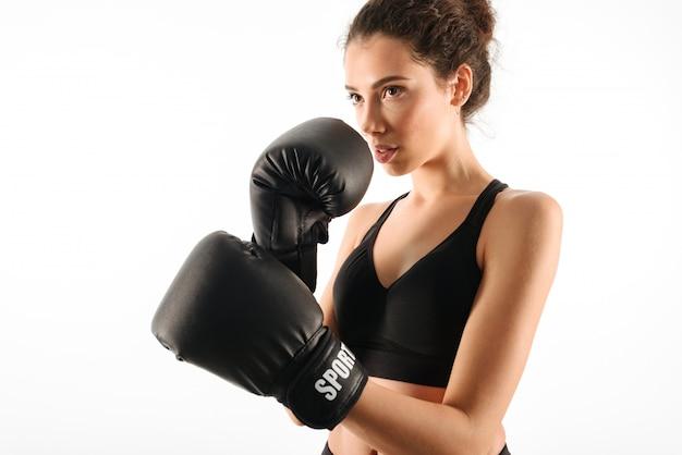 Ernstige krullende donkerbruine geschiktheidsvrouw in bokshandschoenen