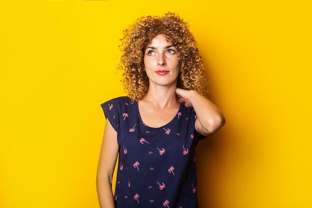 Ernstige krullende jonge vrouw die haar hals met haar hand op een gele oppervlakte houdt