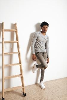 Ernstige latino donkere man draagt lege grijze heide kleding en poseert in de buurt van houten ladder op witte muur, zijaanzicht
