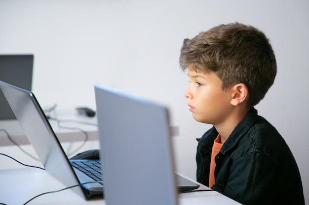 Ernstige leerling aan tafel zitten en kijken naar laptop scherm