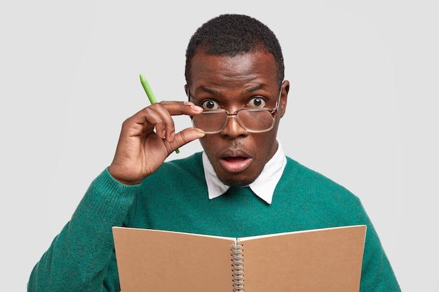 Ernstige leraar houdt hand op frame van bril, houdt pen vast, verrast met studenten uitstekend antwoord op examen, gebruikt kladblok voor het schrijven van notities