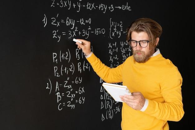 Ernstige leraar met voorbeeldenboek wijzend op vergelijking op bord met krijt terwijl online studenten uitleggen hoe het op te lossen
