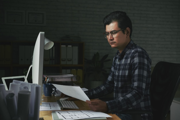 Ernstige man aan het werk met documenten in zijn kantoor