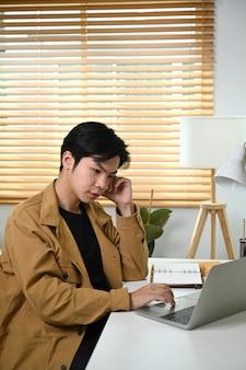 Ernstige man aan het werk online met laptop in de woonkamer.