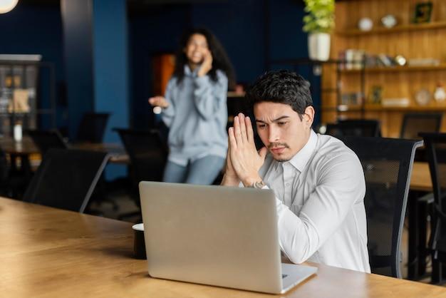 Ernstige man aan het werk op laptop aan het bureau