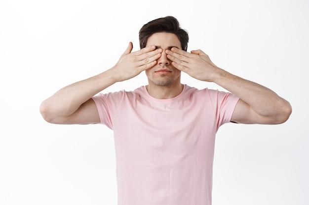 Ernstige man bedek ogen met handen en wacht op iets, anticiperend op verrassing, staande tegen een witte muur
