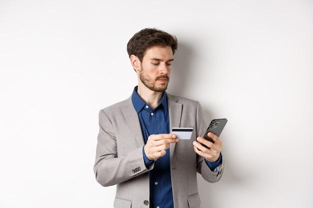Ernstige man betalen met creditcard op smartphone, geld verzenden, permanent in pak op witte achtergrond.