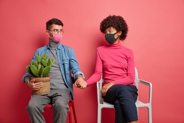 Ernstige man en vrouw die besmet zijn met het coronavirus, steunen elkaar, handen vasthouden, beschermende gezichtsmaskers dragen, op stoelen zitten, vrijetijdskleding dragen, tijd thuis doorbrengen
