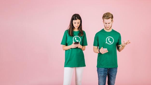 Ernstige man en vrouw die mobiele telefoon op roze achtergrond met behulp van