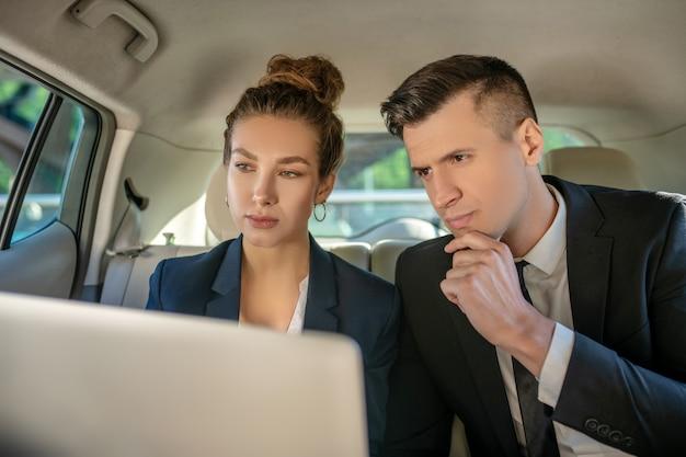 Ernstige man en vrouwenpartners die laptop bekijken