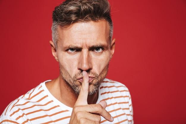 Ernstige man in gestreept t-shirt met wijsvinger op lippen met strikte blik geïsoleerd op rood