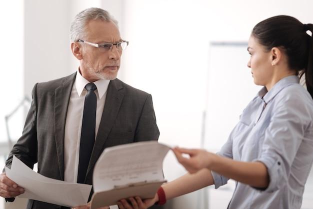 Ernstige man in jaren die zijn voorhoofd rimpelt en documenten in beide handen houdt terwijl hij zijn manager onderzoekt