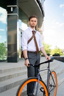 Ernstige man in overhemd, stropdas en broek staat bij zijn fiets terwijl hij het kantoor verlaat en na een werkdag naar huis gaat