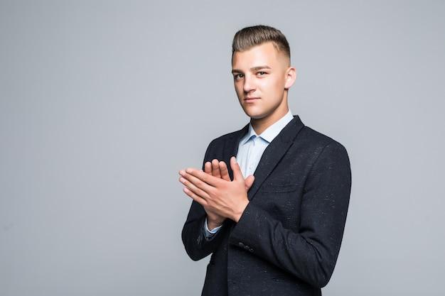 Ernstige man in suite klapt in zijn handen voor lichte muur