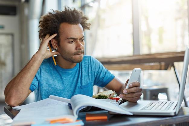 Ernstige man met borstelig haar die met wetenschappelijke literatuur werkt en een artikel schrijft met behulp van moderne technologieën, die probeert de nodige informatie in zijn telefoon te vinden