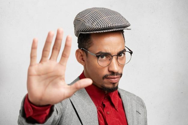 Ernstige man met donkere huidskleur maakt stopgebaar met de handpalm, zegt nee, drukt ontkenning of beperking uit.