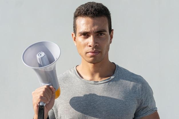 Ernstige man met megafoon klaar voor demonstratie