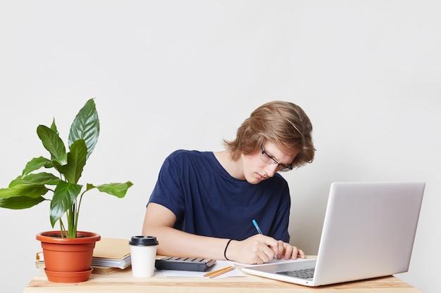Ernstige man met trendy kapsel, draagt casual kleding, zit op de werkplek, bestudeert documenten op een laptopcomputer