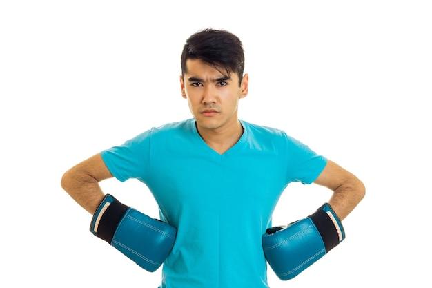 Ernstige man poseren in blauw shirt en bokshandschoenen geïsoleerd op een witte achtergrond in studio