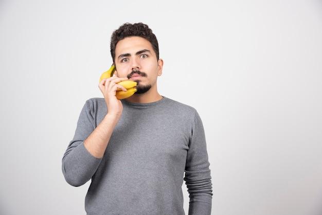 Ernstige man praten met banaan op grijs.