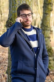 Ernstige man, praten op mobiele telefoon in een herfst park.