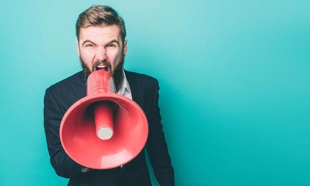 Ernstige man schreeuwt en schreeuwt met behulp van een luidspreker