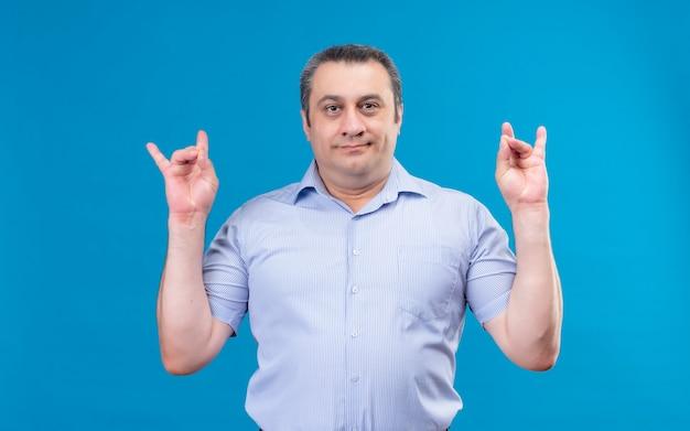 Ernstige man van middelbare leeftijd in blauw gestreept overhemd hand in hand in het rock-symbool op een blauwe achtergrond