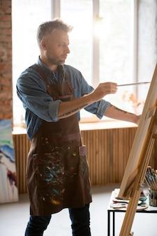 Ernstige man van middelbare leeftijd met penseel kijken naar foto op ezel tijdens het schilderen in zijn atelier of atelier