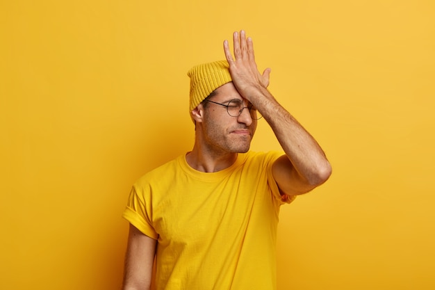 Ernstige man vergat belangrijke vergadering, slaat palm op voorhoofd, heeft spijtgevoelens, herinnert zich de taak, draagt vrijetijdskleding, modellen tegen gele ruimte